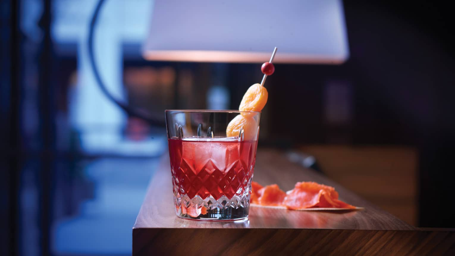Dried apricots on stick in red cocktail in crystal rock glass