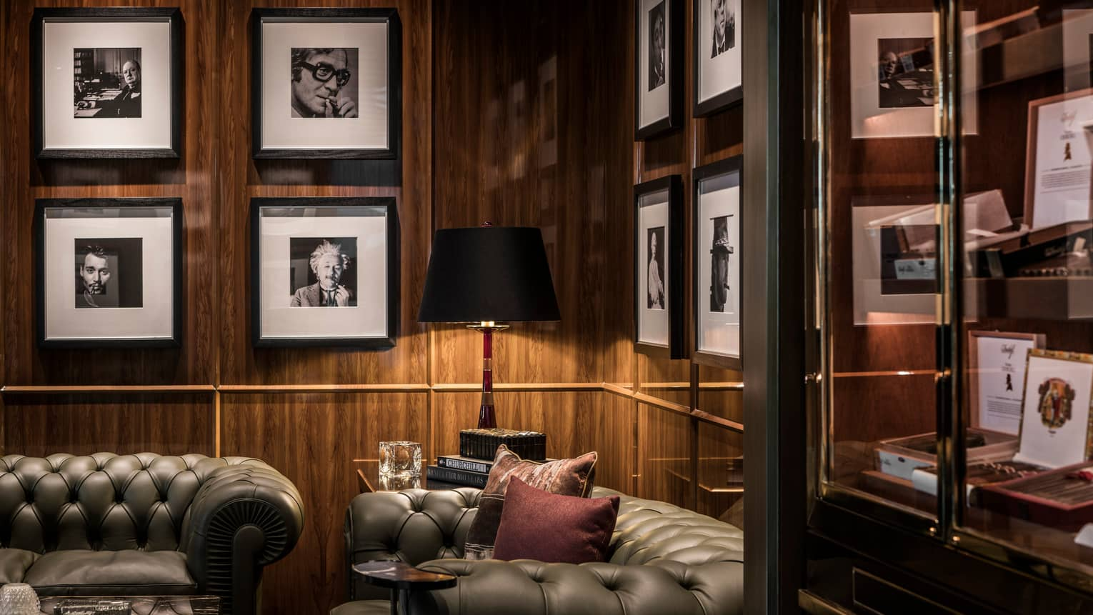 Churchill Club lounge two leather sofas against dark wood wall, framed black-and-white photos on walls