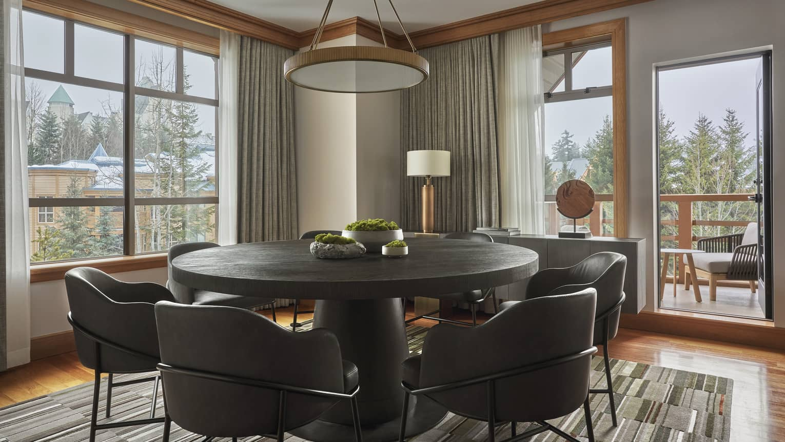 Round dining table with six modern, leather seats and a door leading out to a balcony