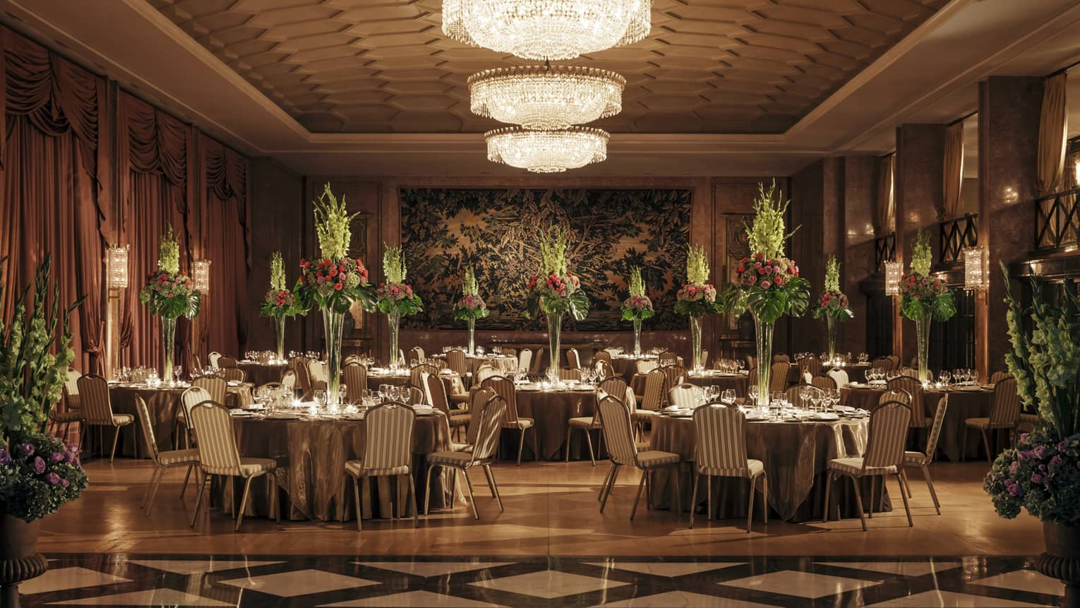 Art Deco-style dining room with tiles, banquet tables with tall flower arrangements, crystal chandelier