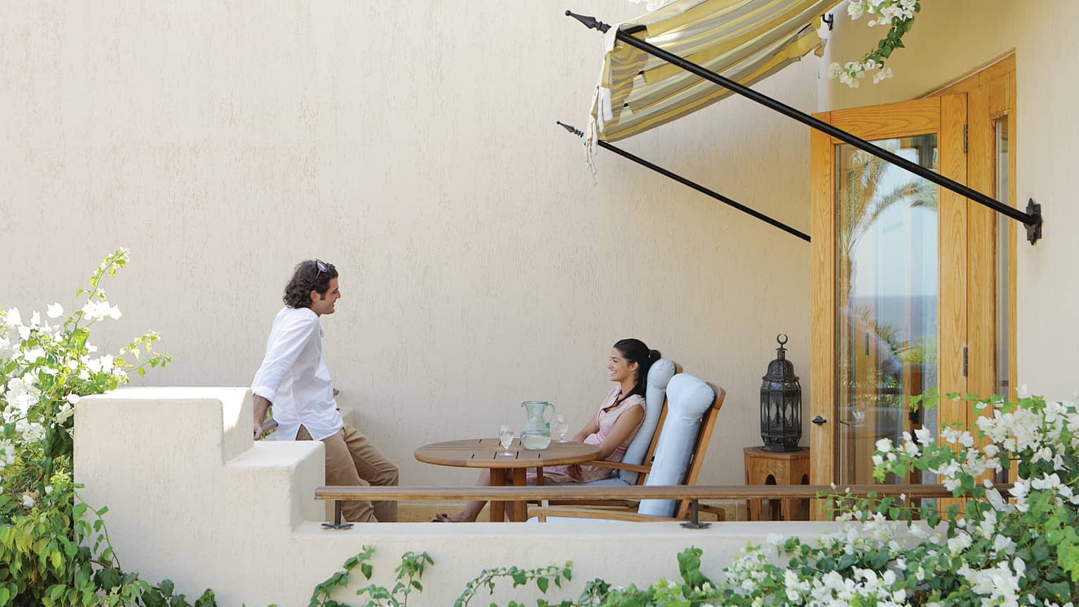 Man and woman relax at private balcony table
