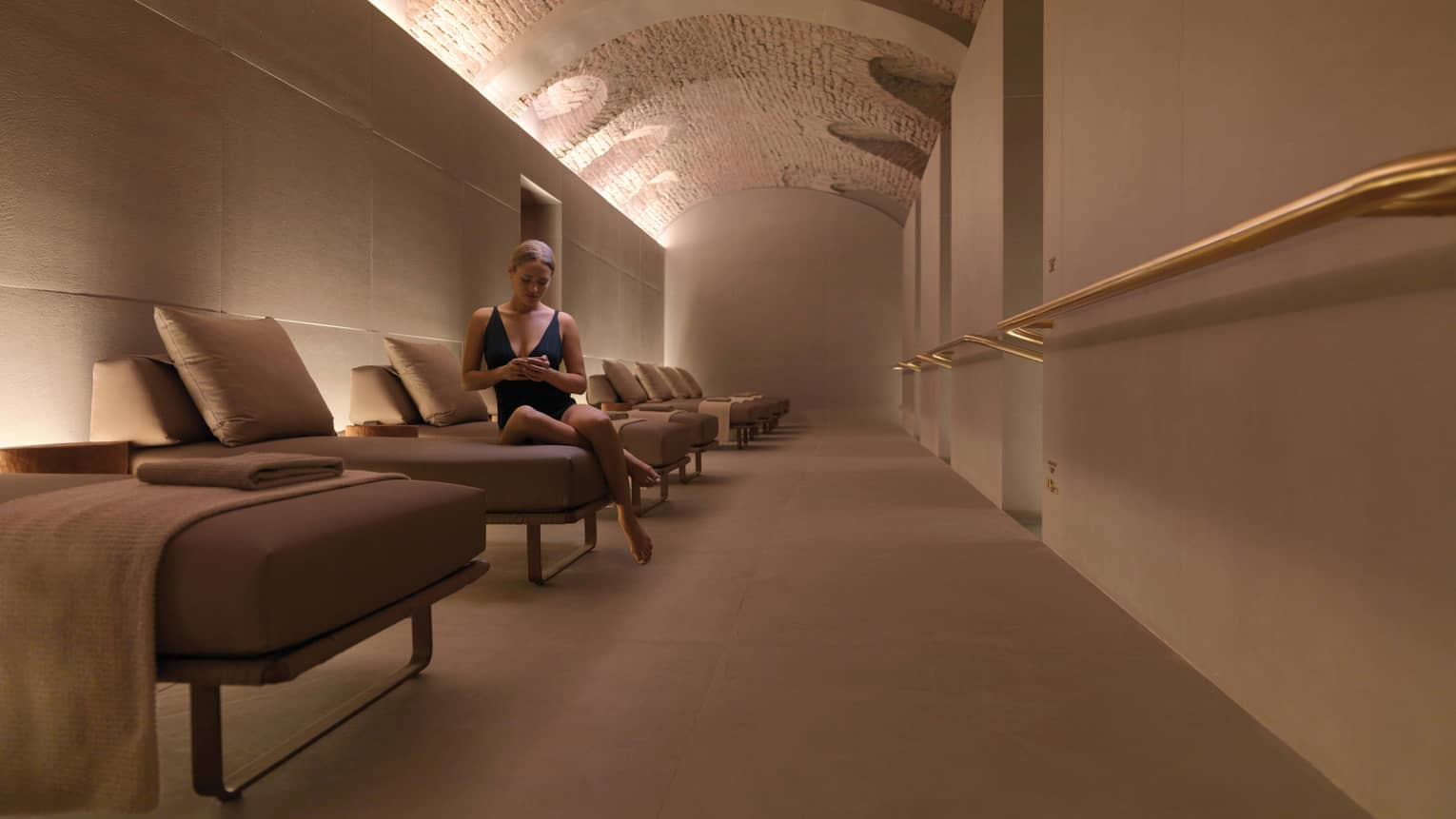 Woman wearing swimsuit sits on end of plush lounge chair in spa under curved stone ceiling