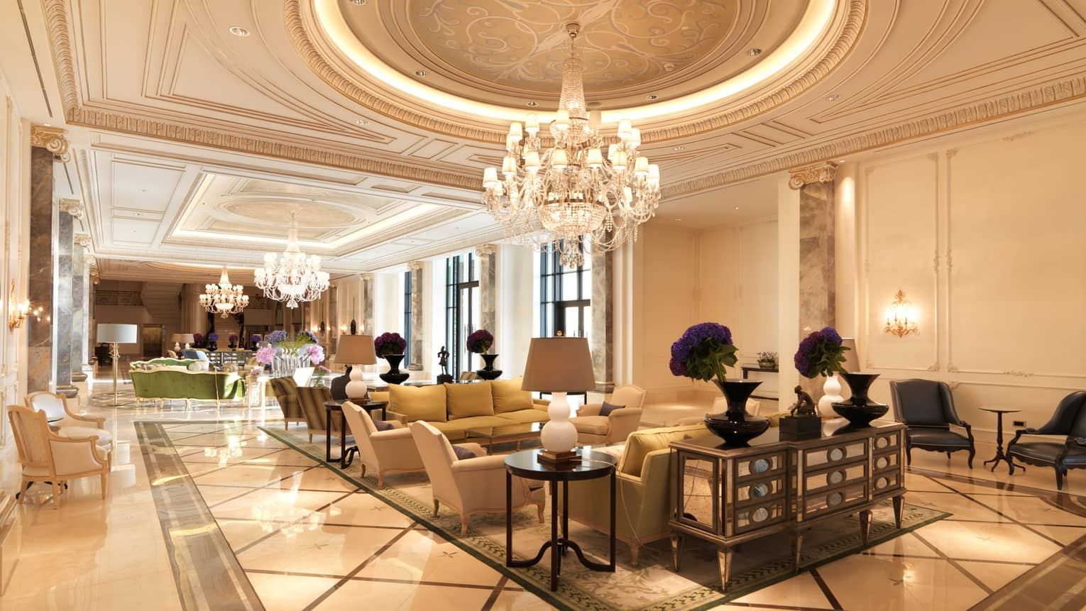 Baku hotel lobby with decorative Beaux-Arts ceiling, three large crystal chandeliers, clusters of armchairs below