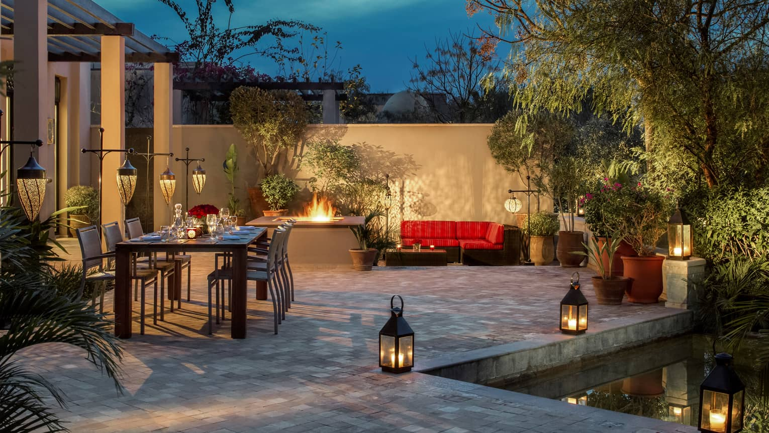 Two-bedroom villa patio with long candle-lit private dining table, outdoor fireplace, lanterns along pool