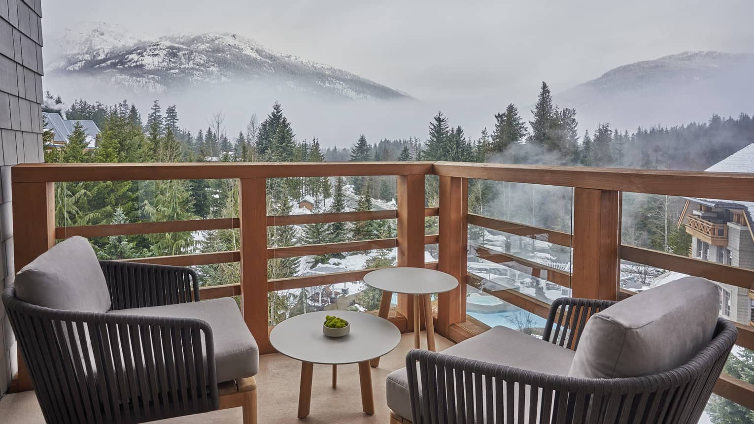 Balcony with two arm chairs and small tables, overlooking Whistler mountains