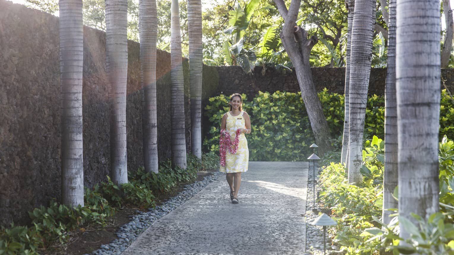 Hotel staff holding fresh flower lei necklace walks down garden path