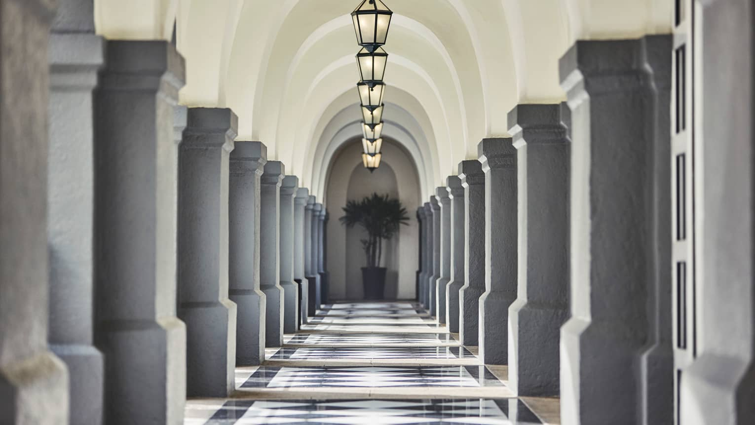 Stone pillars, lanterns down long, sunny outdoor hallway