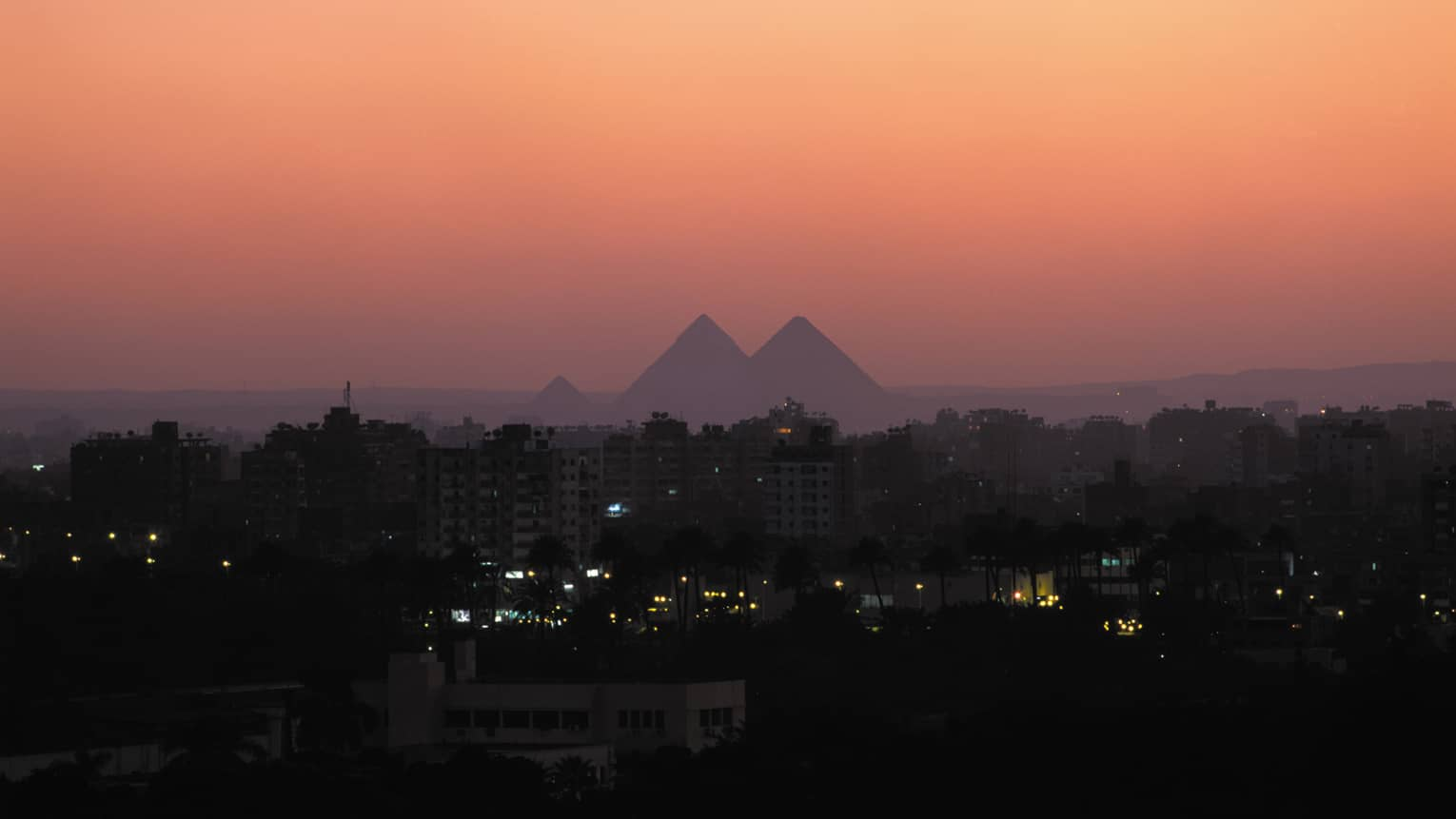 Silhouettes of the Great Pyramids of Giza against a pink sunset