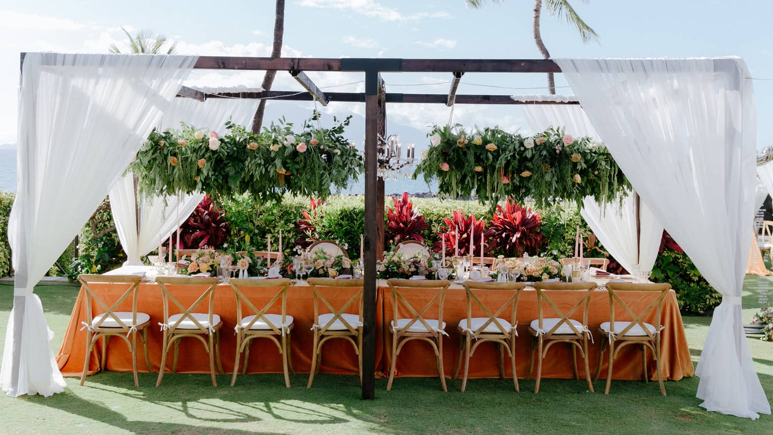 Outdoor wedding reception table under pergola with white curtains