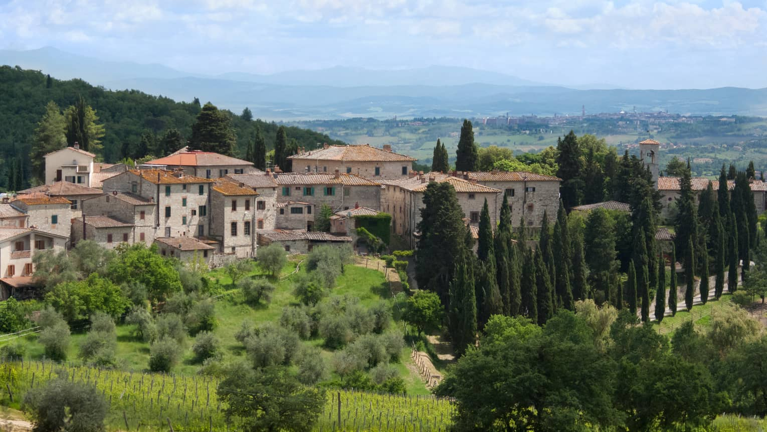 Tuscan countryside with historic stone building against rolling green hills