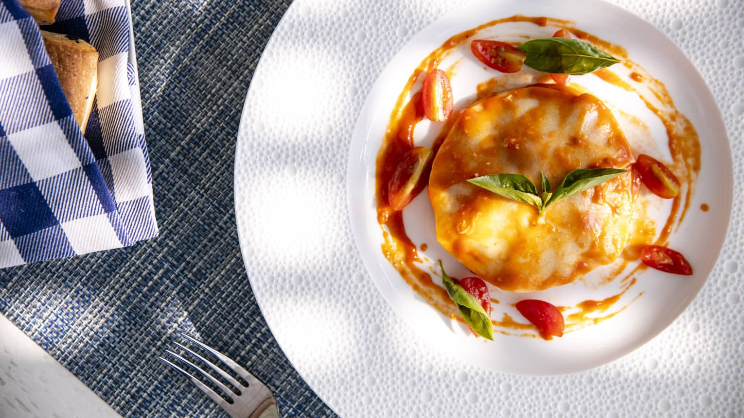 an aerial shot of a tomato and egg dish with basil on top in Four Seasons Maldives - Landaa