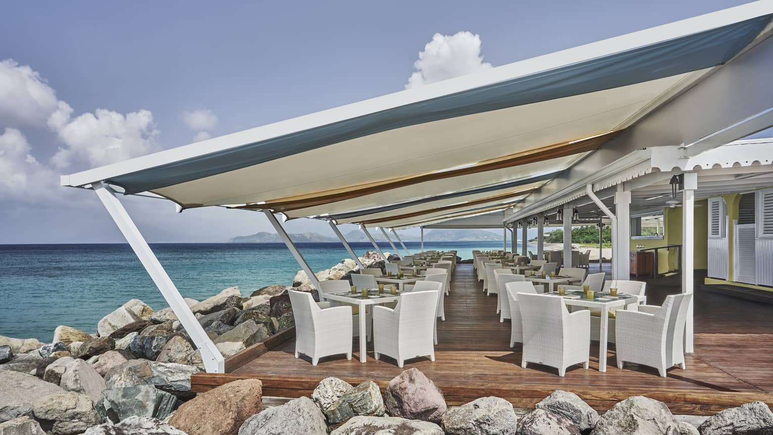 Outdoor restaurant covered by large awning, set next to large rocks and the sea