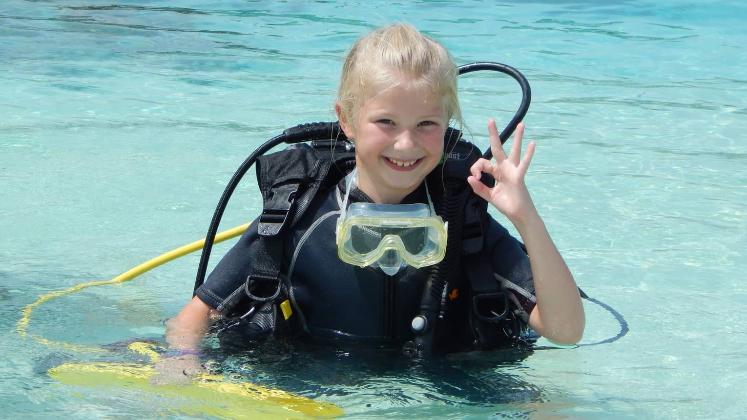 Young girl wearing scuba diving gear in water smiles, gives hand signal