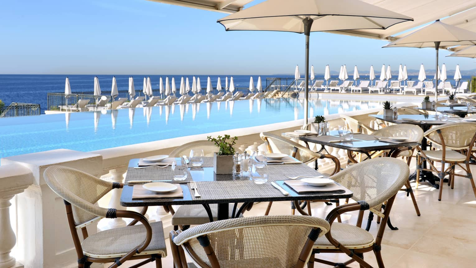 Club Dauphin patio dining tables by outdoor blue swimming pool, sea views