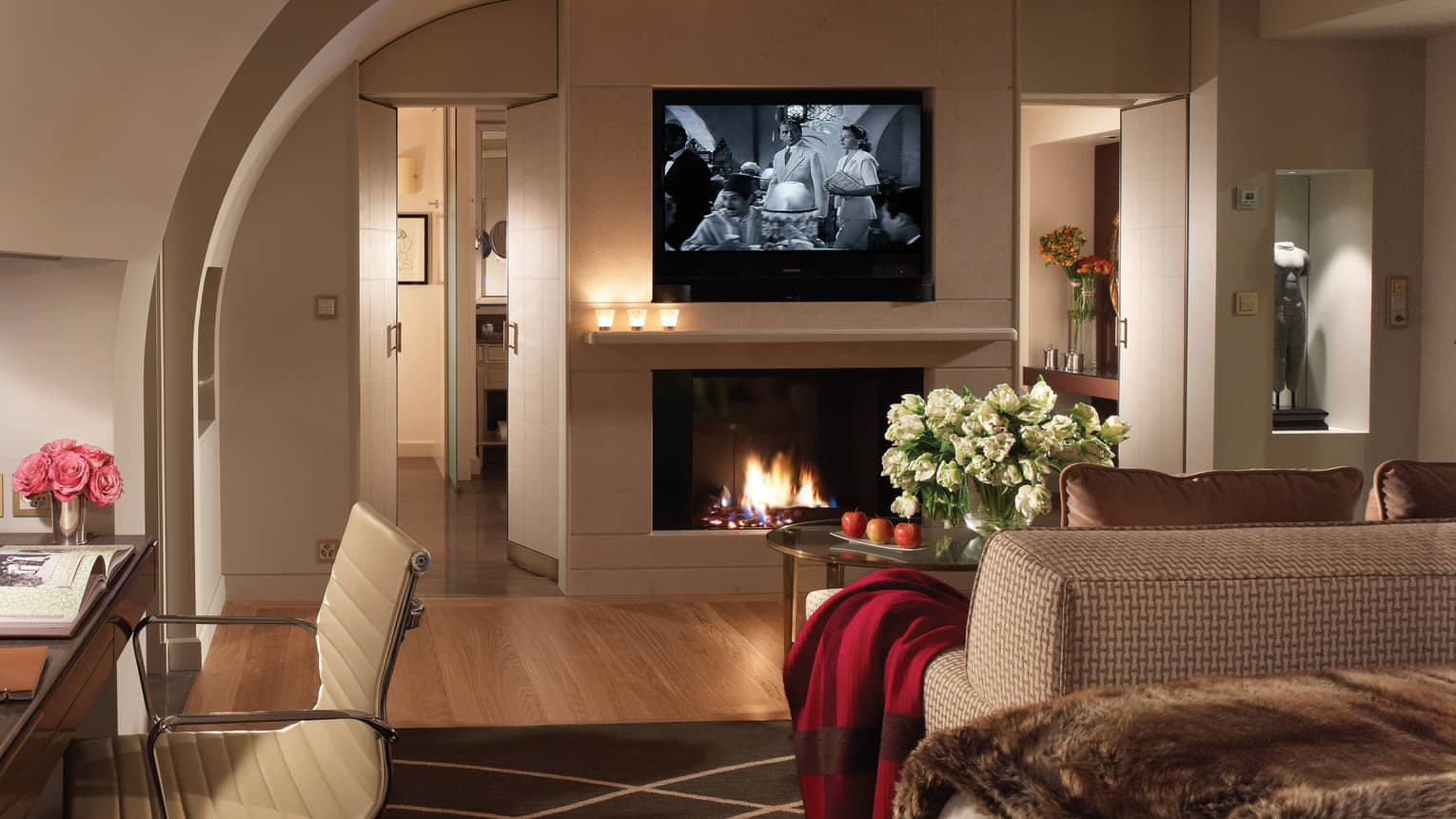 Flat-screen TV showing black-and-white-movie above glass fireplace, sofa with red blanket on arm