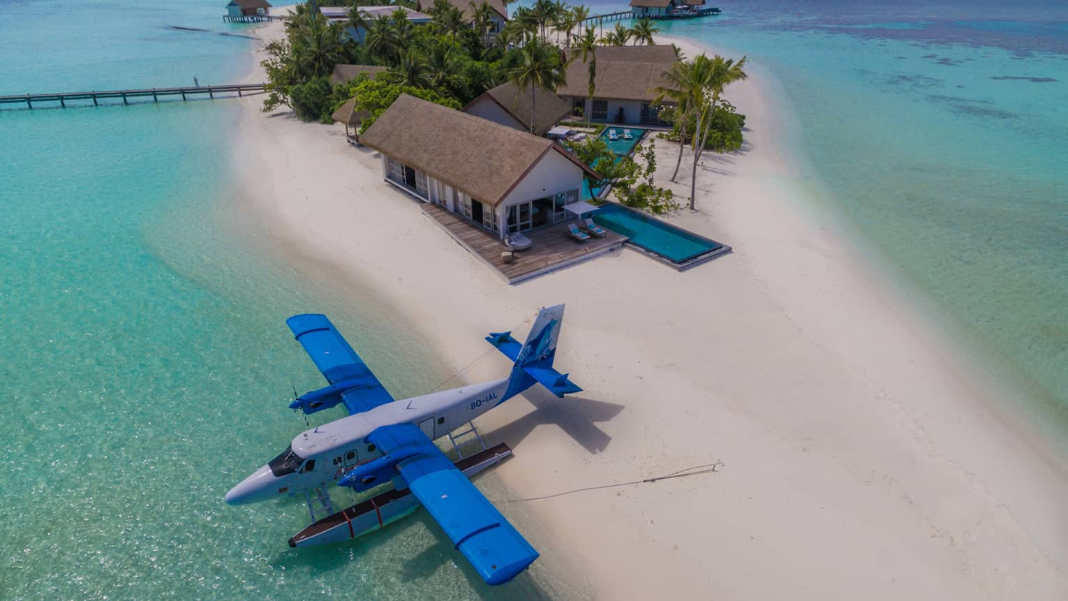 Aerial view of private float plane parked in lagoon by white sand beach, private island