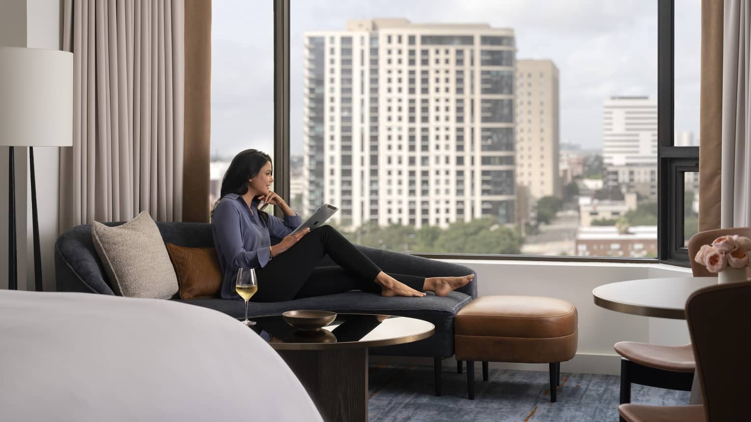 A woman lounging in a hotel room while looking out a large window.