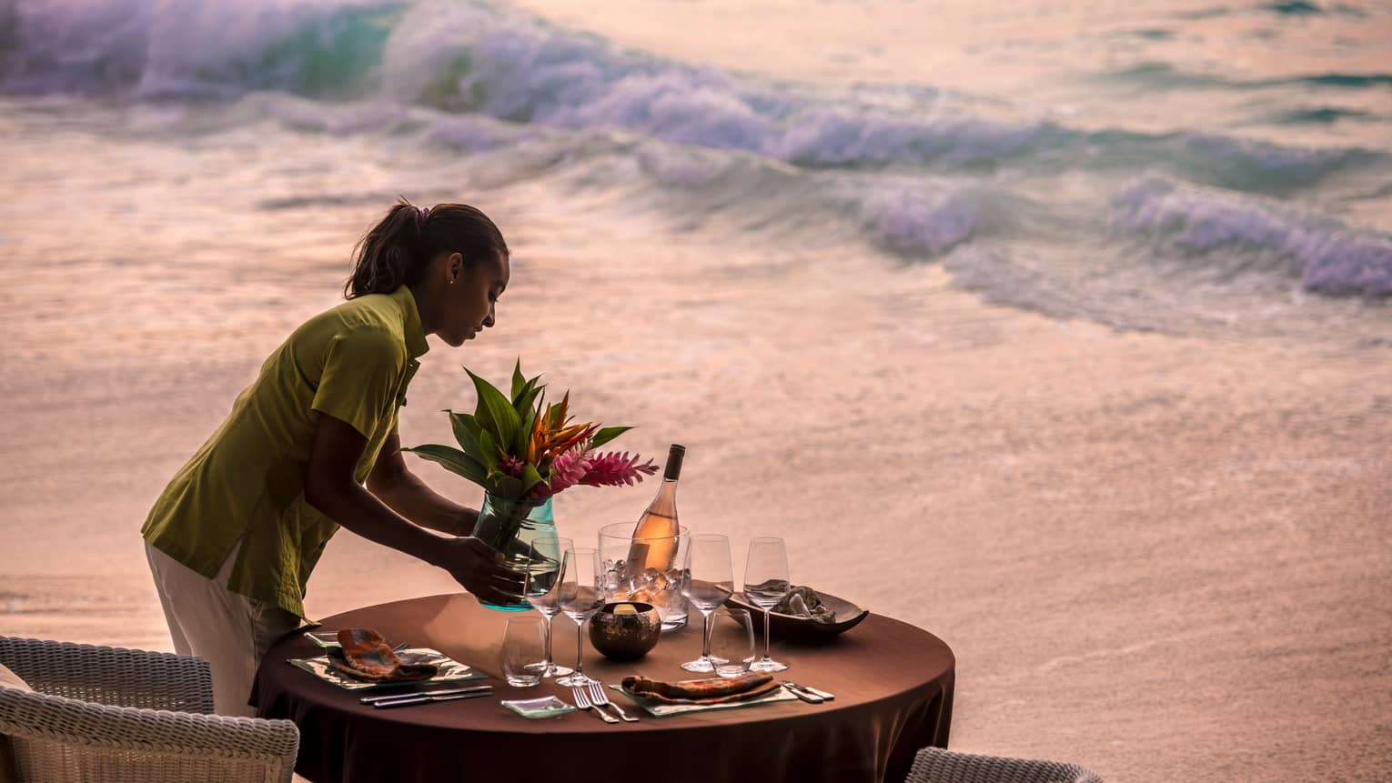 Woman sets vase with flowers on round dining table in front of beach tides at sunset