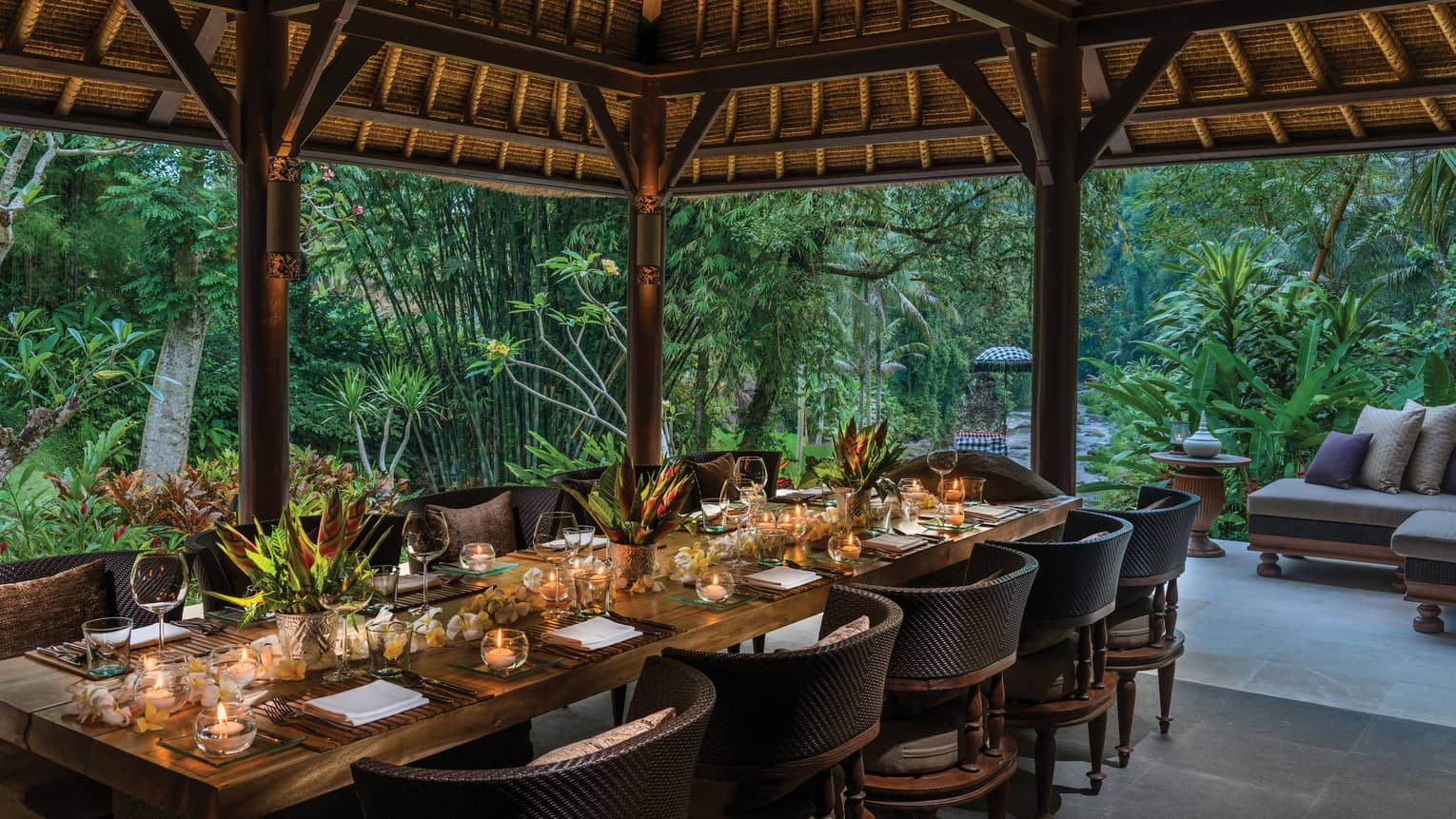 Long private dining table with candles under Royal Villa outdoor pavilion