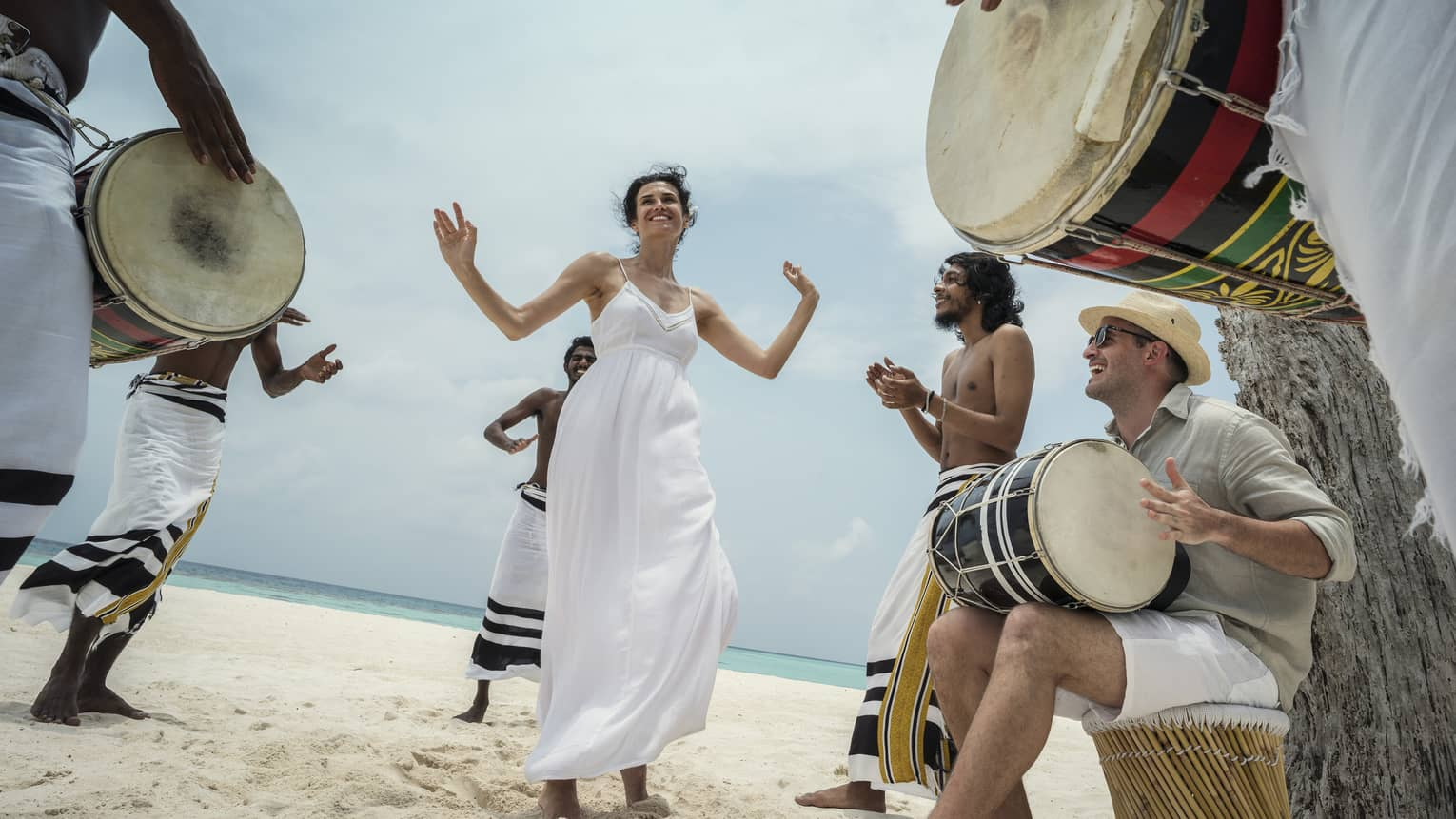 Woman wearing white dress dances in middle of drummers on beach