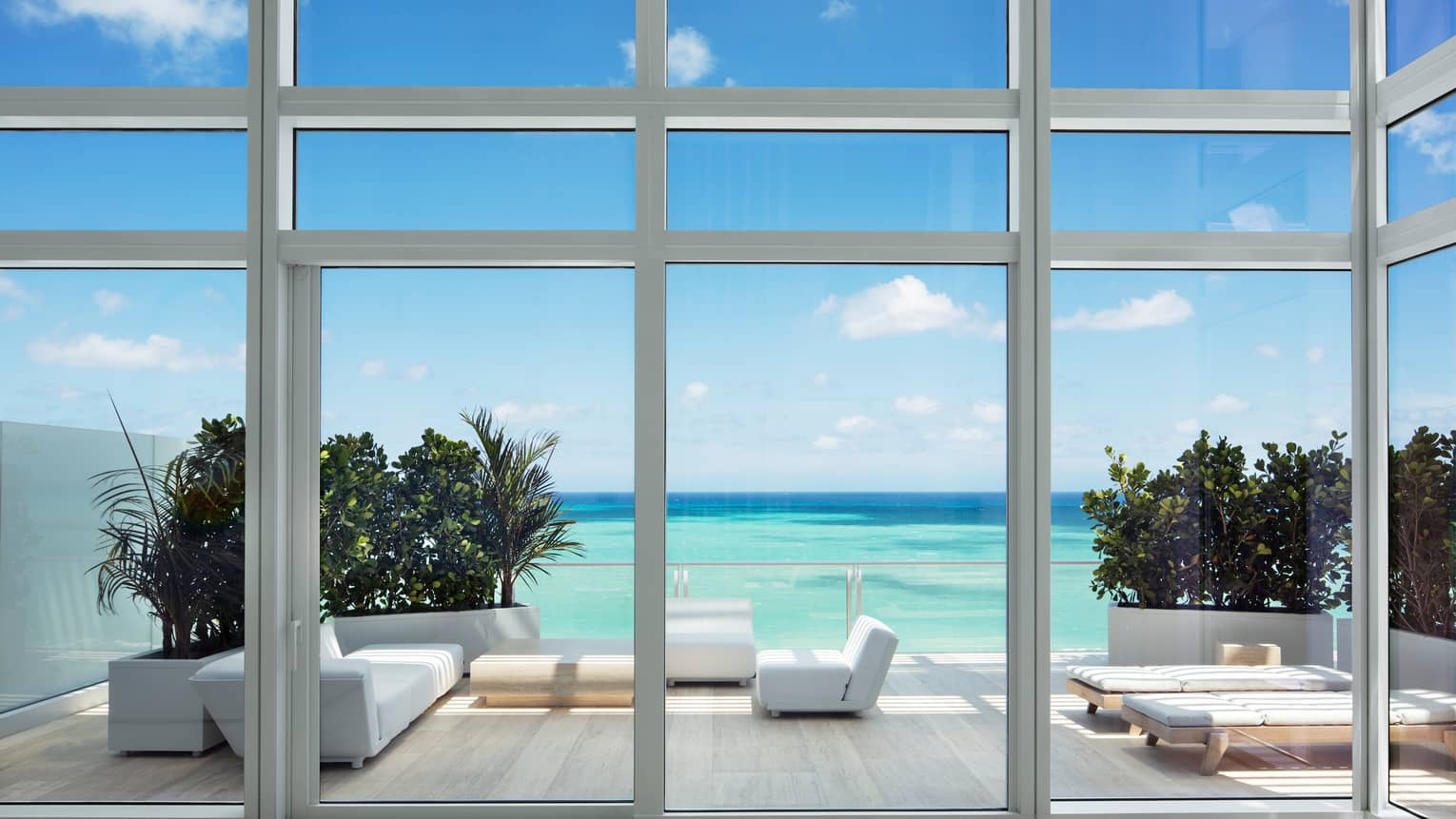 View from glass walls to large patio with modern white furniture, turquoise ocean