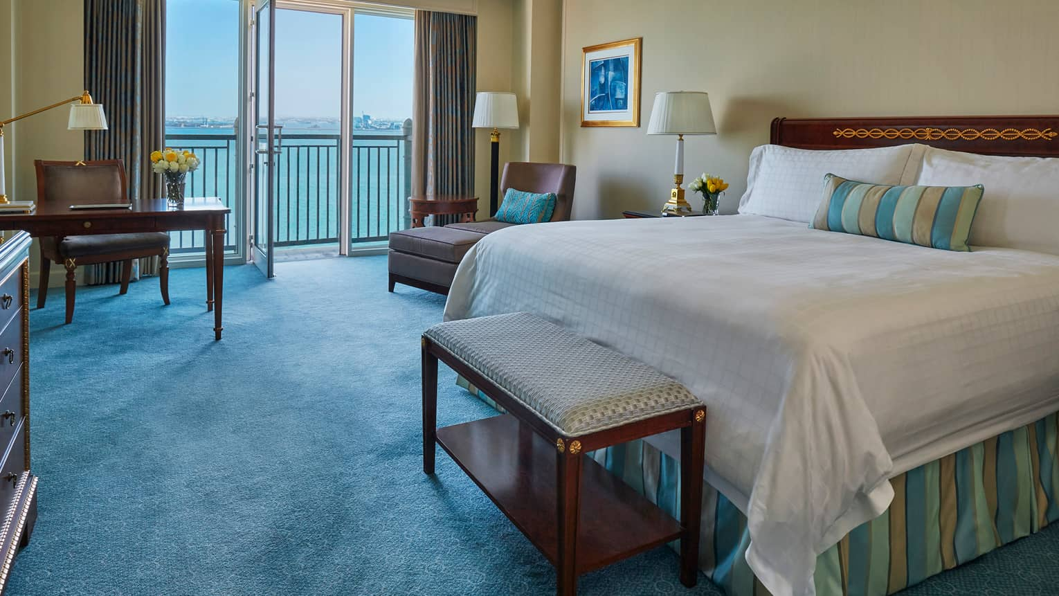 Premier Room with open glass balcony door, ocean view, blue carpet, bed with striped accent pillow