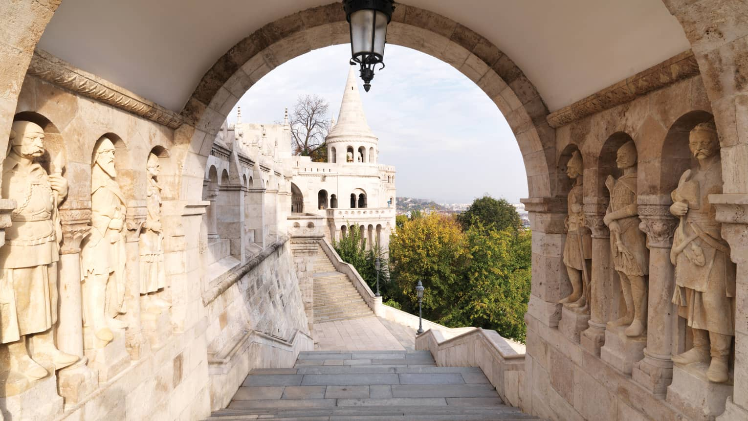 View down Fisherman's Bastion landmark stairs past stone carvings of statues in wall to castle-like turret
