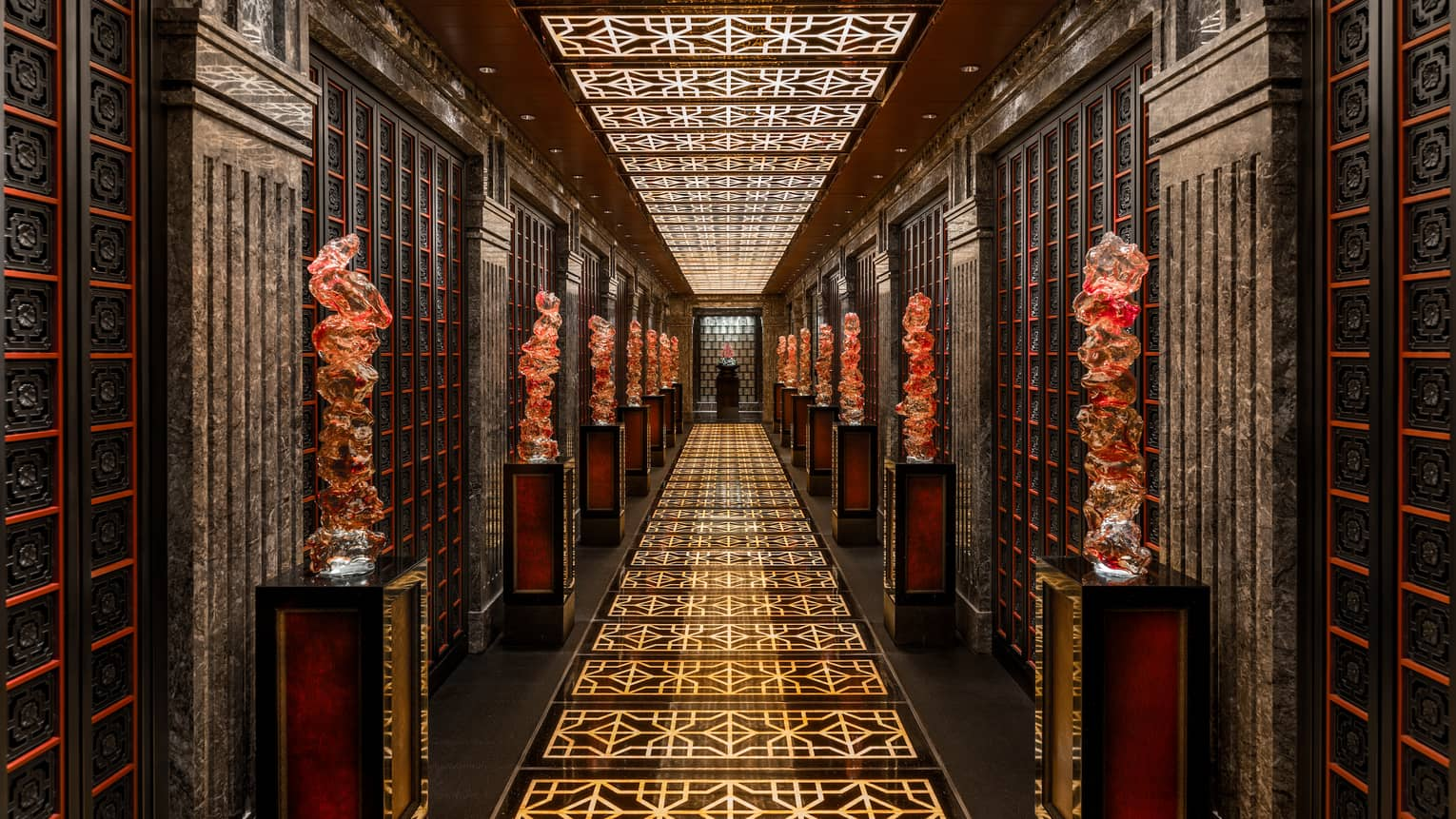 Long dimly-lit hallway at Cai Yi Xuan restaurant with gold pattern on floor, large red statues on pillars