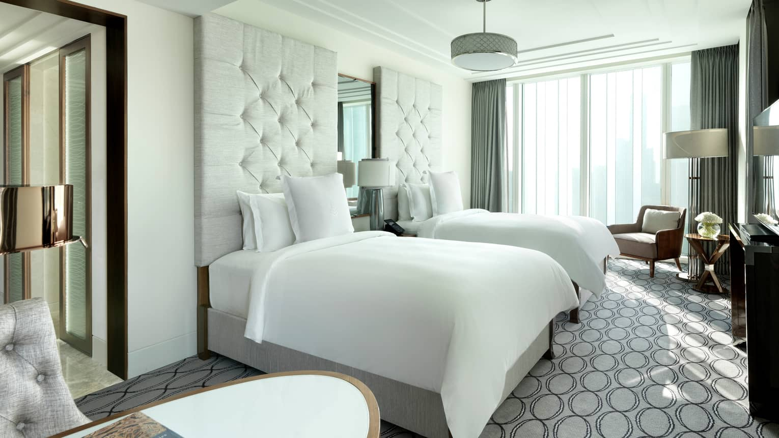 Premier Room double beds with white linens, headboards, grey patterned carpet