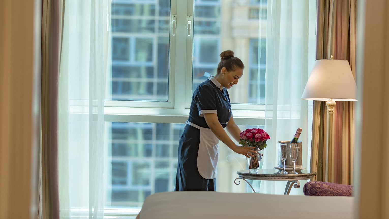 A housekeeper places a vase of pink roses on a bedside table