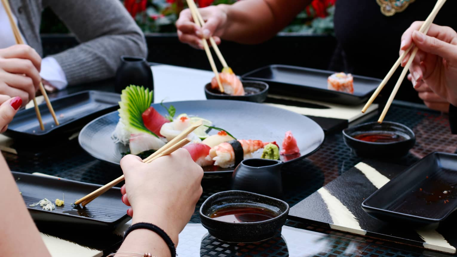 Close-up of four sets of hands holding chopsticks around black plate with sushi rolls, bowls of soy sauce