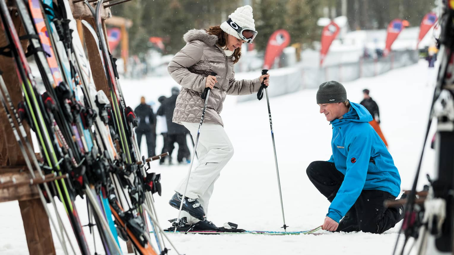 Hotel staff holds skis as woman holding poles steps in by ski rack, snowy hill