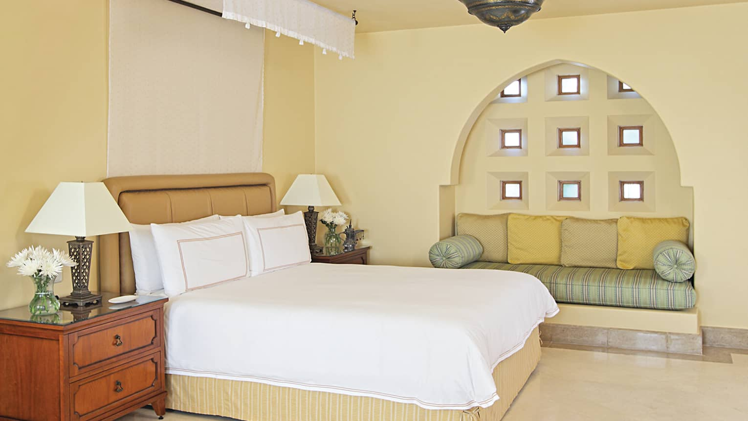 Hotel room bed, padded headboard, nightstands with lamps and flowers beside cushioned window seat