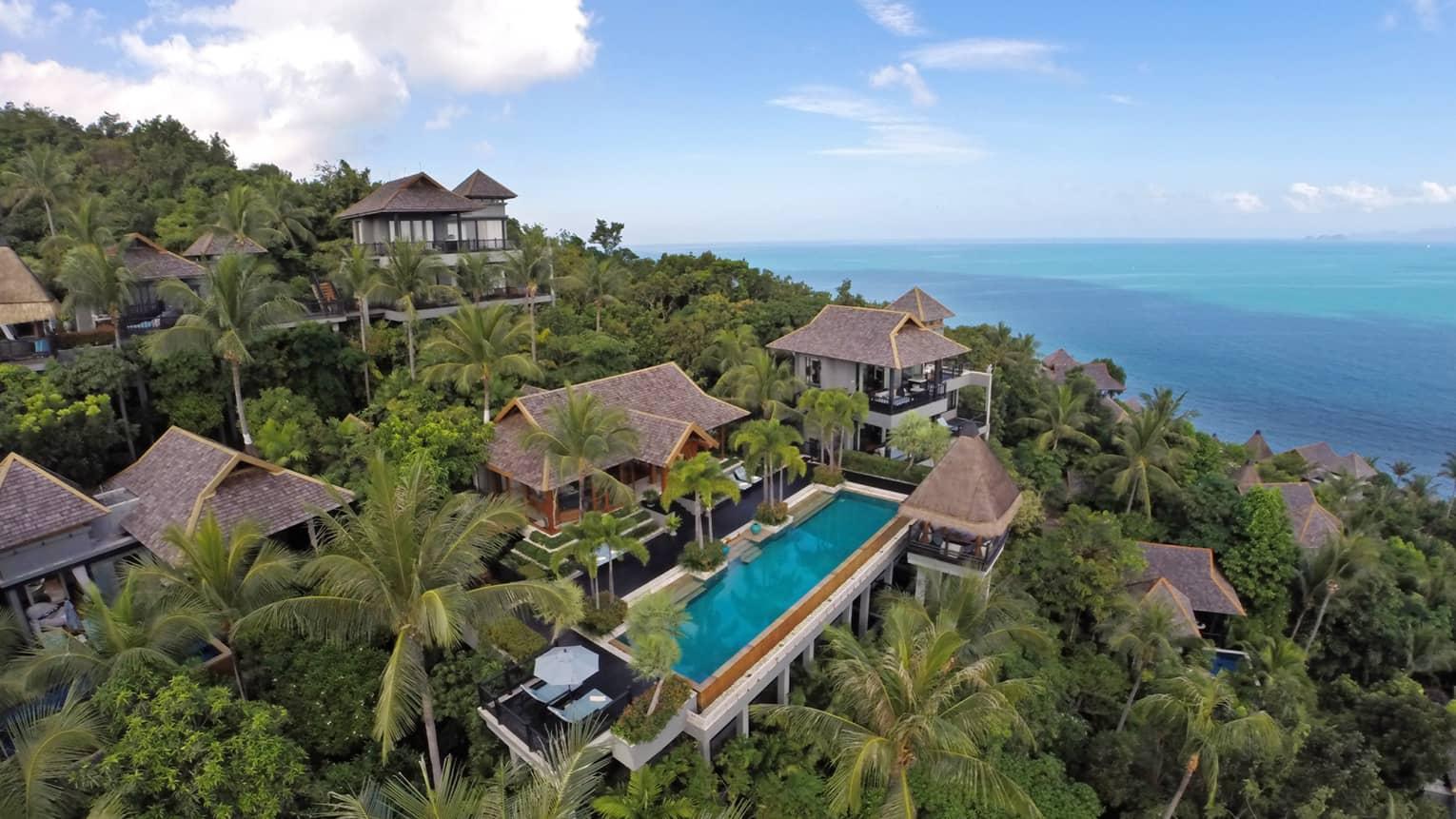 Aerial view of owner's residence villa complex around blue swimming pool, patio on tropical mountain
