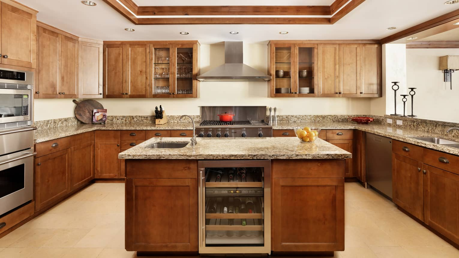 A fully furnished kitchen with granite countertops and an island with a wine chiller