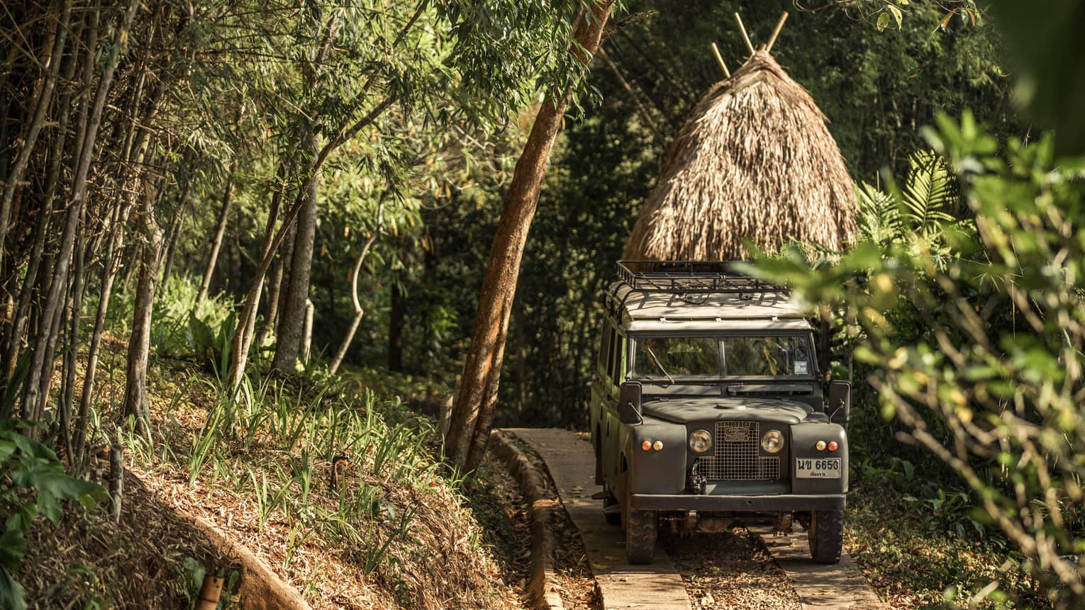 Jeep driving down path in forest past thatched-roof hut