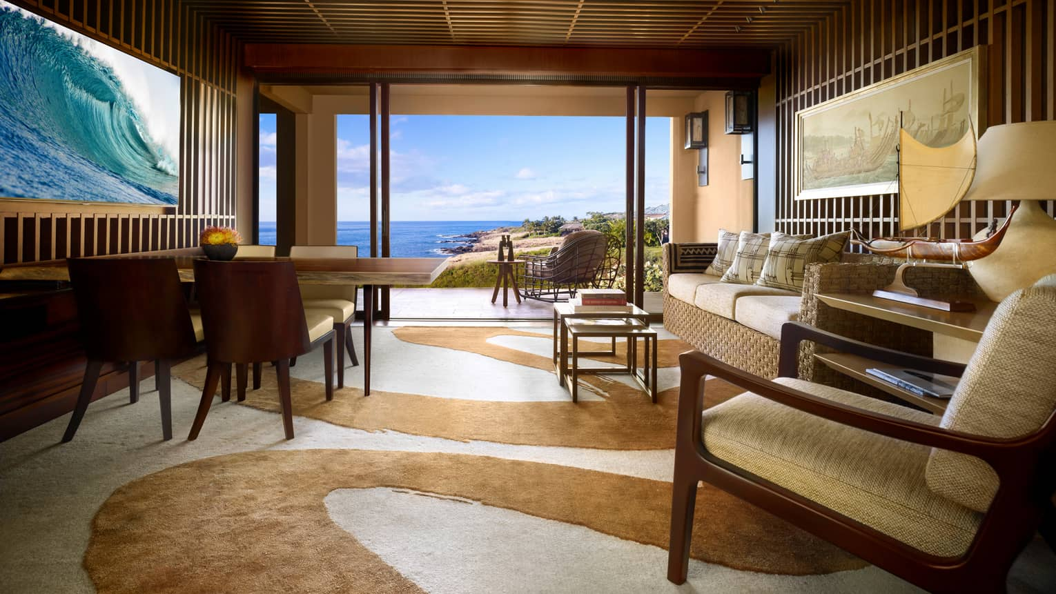 Ohana Ocean-View Suite teak-panelled walls, wave screen over wood dining table, sofa, swirl-patterned carpet