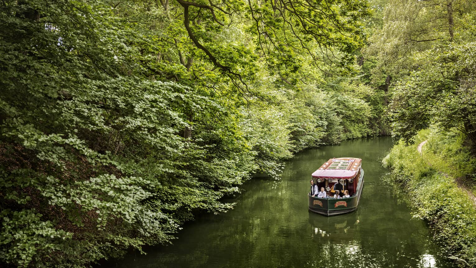 Family on canal boat Louise rides along forest-lined river