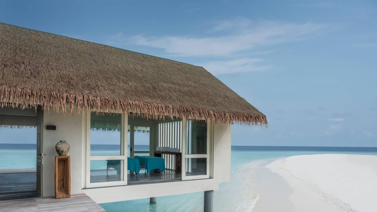 Exterior view of thatched roof spa with massage beds in open-air room over lagoon