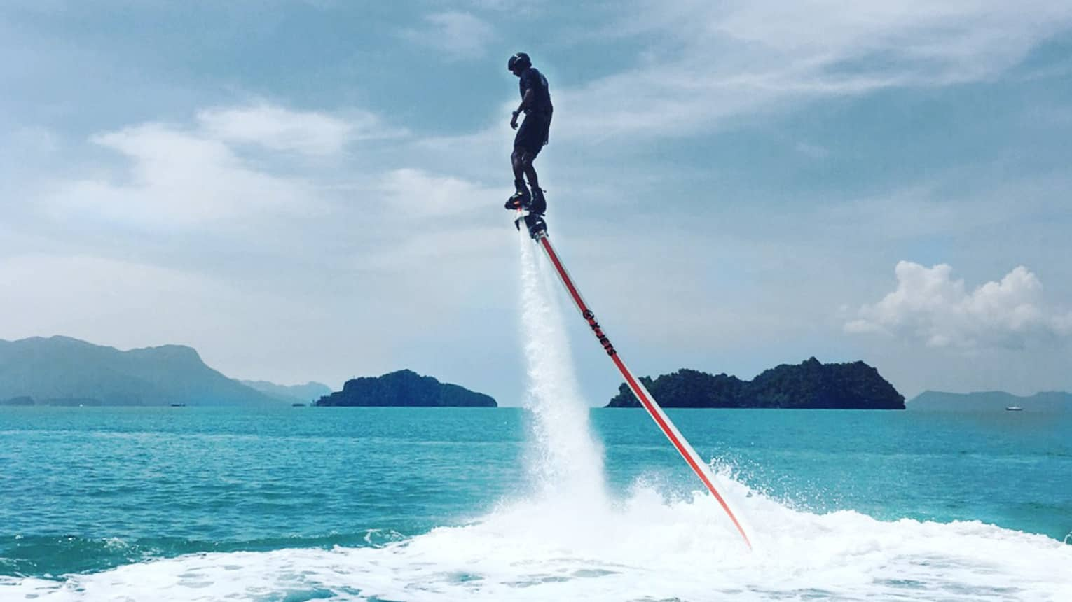 Water sprays as man soars above ocean attached to line, jet blade pack