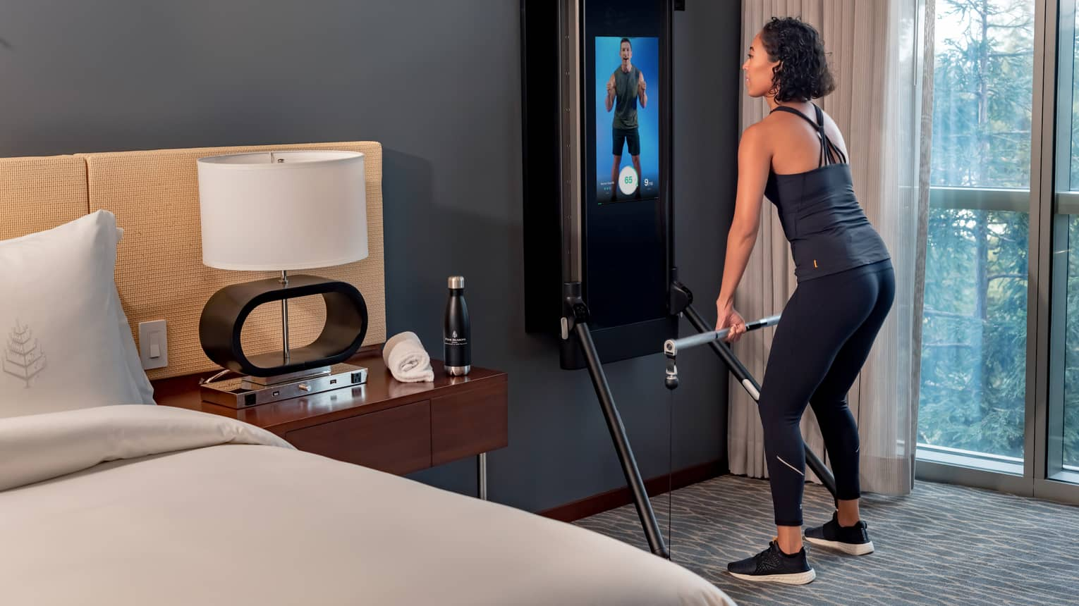 Woman exercises in front of an instructor on a screen in a Tonal technology-equipped guest room
