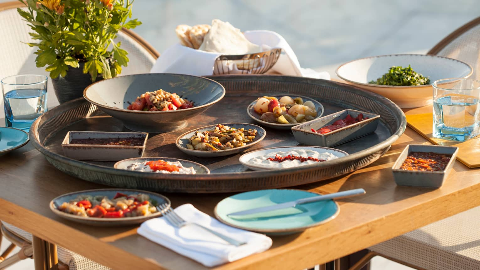 Small dishes of vegetables, salads on large tray on patio table
