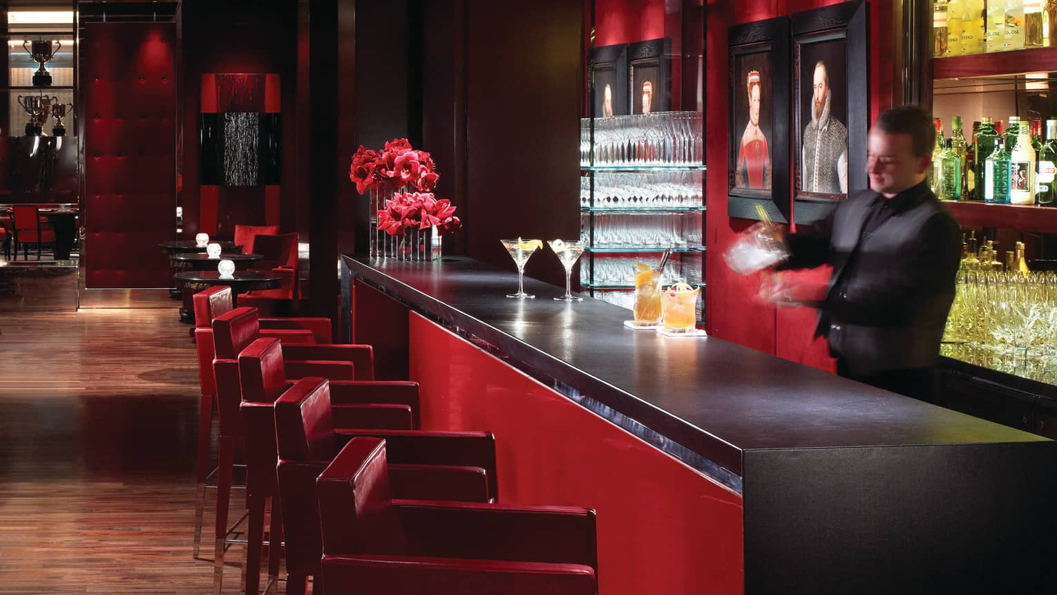 Bartender shaking cocktail behind Amaranto bar lined with red stools, martinis, flowers