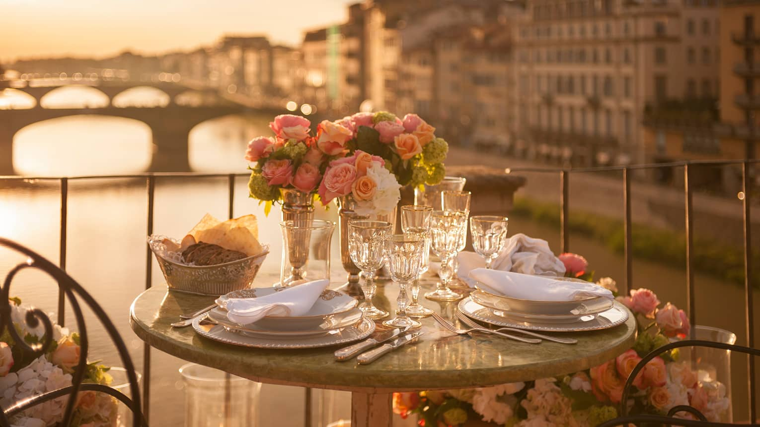 A romantic table for two is set with white porcelain plates, crystal glasses, pink roses on a balcony overlooking a bridge and historic building in Florence