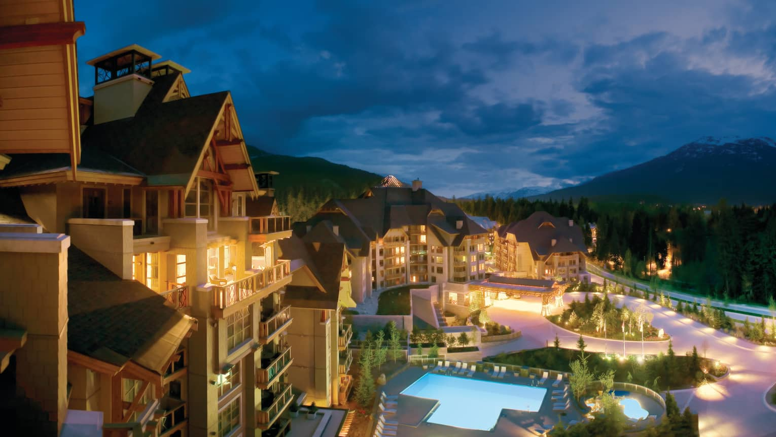 Exterior view of Four Seasons resort at night with swimming pool and mountains in background