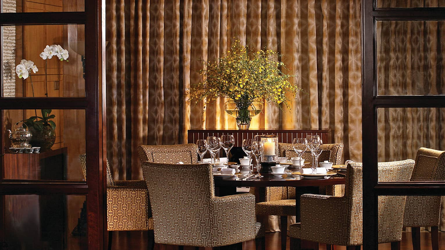 Upholstered dining chairs around wood table in dimly-lit dining area by wall, curtains