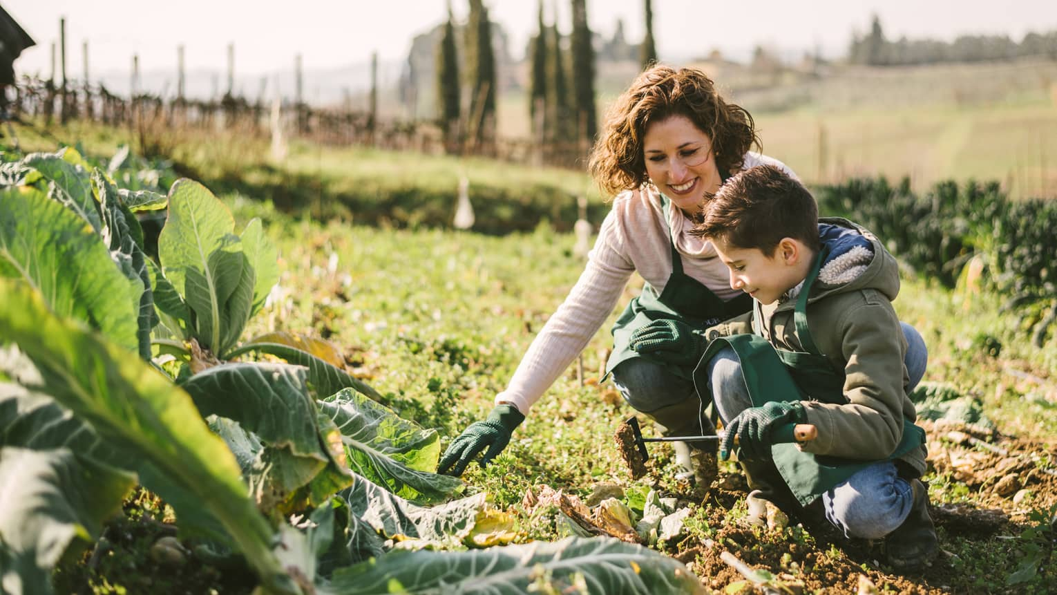 Woman and boy wearing aprons, gloves kneel in soil near large lettuce leaves in vegetable garden patch