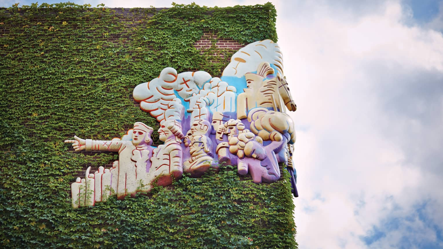 Artistic sculpture on corner of brick building covered in ivy