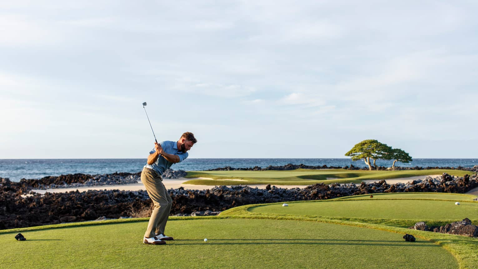 Man swings golf club on Hualalai Golf Course green by ocean