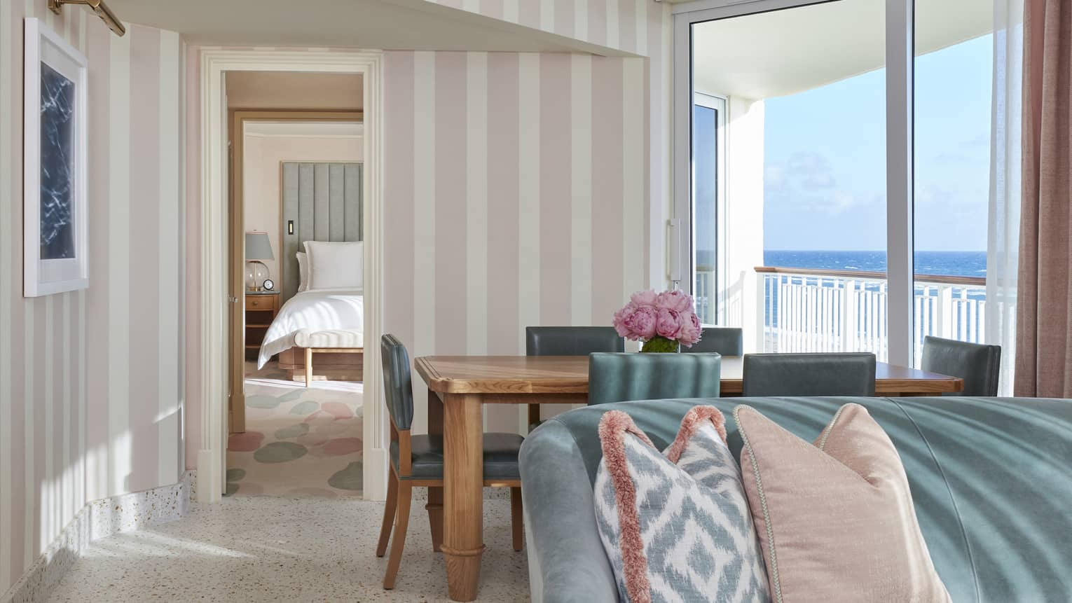 Ocean Grand Suite's living area, featuring a sofa, dining table and light pink- and white-striped walls